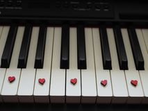 Romantic music, a piece of piano, white and black keys with small red hearts royalty free stock photo