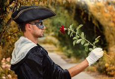 Romantic mystery man holding a rose. Romantic mystery man in black mask and velvet cape holding a red rose. Selective focus Stock Photo