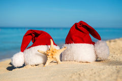 Romantic New Year at Sea. Christmas vacation. Santa hats on sandy beach Stock Photos