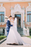 Romantic newly married couple charming bride and stylish groom holding each other in front of antique building entrance Stock Photography