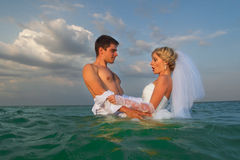 Newly-married couple swimming in sea Stock Images