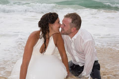 Romantic newly-married couple.Young groom kissing his bride in sea Royalty Free Stock Photos