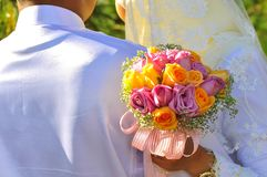 Malay Couple hold Wedding Flower Bouquet. Romantic newly wed malay couple hug each other while holding a flower bouquet at the back Royalty Free Stock Photos