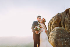 Romantic newlywed couple in autumn sunset lights on majestic rocky mountain cliff.  stock photography