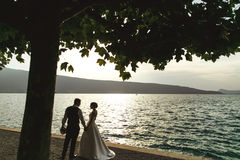 Romantic newlywed couple bride and groom at sunset beach near se Stock Image