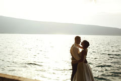 Romantic newlywed couple bride and groom at sunset beach near se Stock Photography