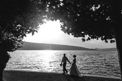 Romantic newlywed couple bride and groom at sunset beach near se Royalty Free Stock Photos