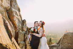 Romantic newlywed couple holding each other in sunset lights  with rocky landscape as backround Stock Images