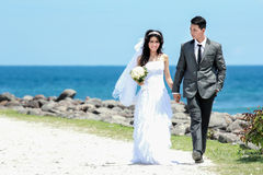 Romantic newlywed couple holding hand and walking at seashore. Full body portrait of romantic newlywed couple holding hand and walking at seashore in sunny day Royalty Free Stock Photography