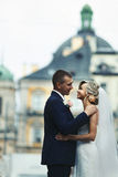Romantic newlywed couple hugging in front of old church.  Royalty Free Stock Image