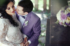 Romantic newlywed couple kissing under tree, bouquet on stairs Stock Images