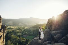 Romantic newlywed couple posing in sunset lights on majestic roc. Beautiful wedding couple bride and groom at wedding day outdoors on the mountains rock on sea Stock Image