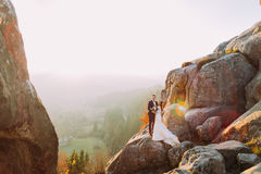 Romantic newlywed couple posing in sunset lights on majestic rocky mountain cliff with rural view as background.  royalty free stock photo