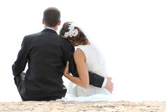 Romantic newlywed couple sitting on seashore. Back view of romantic newlywed couple sitting on seashore with copy space Royalty Free Stock Images