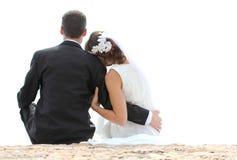 Romantic newlywed couple sitting on seashore Royalty Free Stock Images
