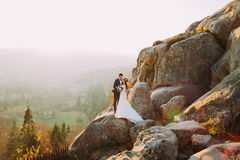 Romantic newlywed couple in sunset lights on majestic rocky mountain cliff with rural view as background.  royalty free stock image