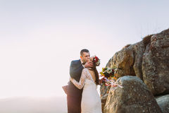 Romantic newlywed husband kissing hin new wife in sunset lights on majestic rocky mountain cliff.  stock images