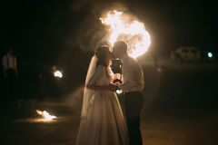 Romantic newlyweds kissing at night in front of flaming heart Royalty Free Stock Photos