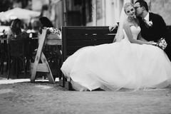 Romantic newlyweds kissing on wooden bench in old french town b& Royalty Free Stock Photos