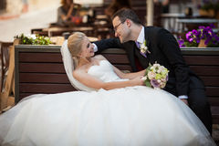 Romantic newlyweds smiling on wooden bench in old french town Stock Images
