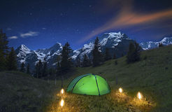 Camping in the Swiss Alps. Romantic torches in front of an illuminated tent and the famous Eiger, Mönch and Jungfrau in the background. Near Interlaken Stock Photo