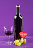 Romantic night. Wine in a glass, a bottle of wine, grapes and a heart with the words I love you Stock Image