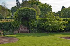 Romantic nook with wood bench and hedge Royalty Free Stock Images