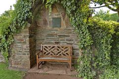 Romantic nook with wood bench and hedge for repose Royalty Free Stock Images