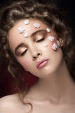 Romantic nude young beautiful girl. With white flowers on her face and soft curls on dark background. Eyes closed. Beauty portrait. Creative make up. Dark Royalty Free Stock Photography