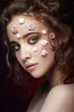 Romantic nude young beautiful girl with white flowers on her face and soft curls on dark background. Looking. Beauty portrait. Creative make up. Dark royalty free stock images