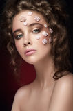 Romantic nude young beautiful girl with white flowers on her face and soft curls on dark background. Looking. Beauty portrait. Creative make up. Dark stock image