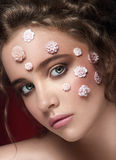 Romantic nude young beautiful girl with white flowers. On her face and soft curls on dark background. Looking up. Beauty portrait. Creative make up. Dark Stock Photography