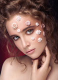 Romantic nude young beautiful girl with white flowers on her face and soft curls on dark background. Touching her face. Looking. Beauty portrait. Creative make royalty free stock photos