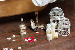 Romantic objects in bathroom. Romantic objects (candles, bird-cages, rose petals, shoes, empty bottle) after relaxing in bath Royalty Free Stock Photography