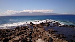 Waters of blue ocean splashing against the stones in sunny day on maui,hawaii stock video footage
