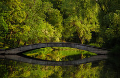 Romantic old stone bridge over a pond in a park Stock Images