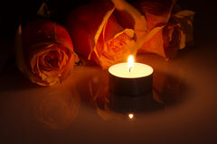 Romantic: orange roses in candlelight. Three yellow-red roses and burning candle in the dark Stock Photos