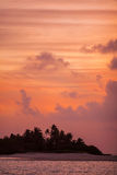 Romantic orange sunset with tropical island, Maldives Stock Images