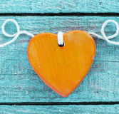 Romantic orange wooden heart on turquoise wood Royalty Free Stock Images