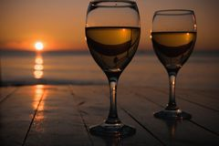 Romantic outdoor activity. Two glasses with white wine in an outdoor restaurant with sunset sea view, relaxation concept for two. Space for text Royalty Free Stock Images