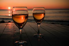 Romantic outdoor activity. Two glasses with white wine in an outdoor restaurant with sunset sea view, relaxation concept for two. Space for text Stock Photography