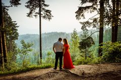 Romantic outdoor full-length portrait. Attractive couple is tenderly looking at each other with the smile while holding. Hands on the green rock during the Stock Photography