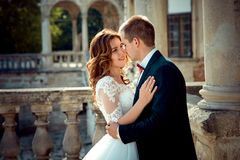 Romantic outdoor portrait of the beautiful happy newlywed couple tenderly rubbing noses. Romantic outdoor portrait of the beautiful happy newlywed couple Stock Images