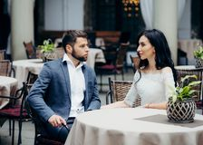 Romantic outdoor portrait of the wedding couple looking at each other while sitting at the restaurant table. Romantic outdoor portrait of the wedding couple Stock Image