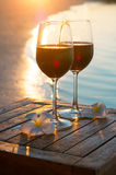 Romantic outdoor scene: two glasses of red wine at sea sunset royalty free stock images