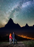 Romantic pair holding hands, standing on a hill and enjoying incredibly beautiful starry sky and Milky way at night Royalty Free Stock Image