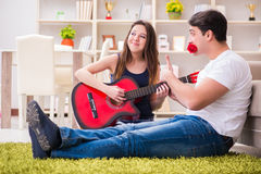 The romantic pair playing guitar on floor Stock Photos