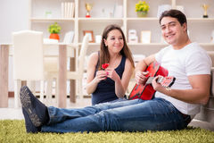 The romantic pair playing guitar on floor Royalty Free Stock Photos