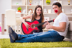 The romantic pair playing guitar on floor Royalty Free Stock Photography
