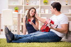 The romantic pair playing guitar on floor Stock Photo